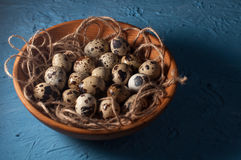 huevos de codornices en cuenco de madera en cierre azul del fondo para arriba Fotos de archivo