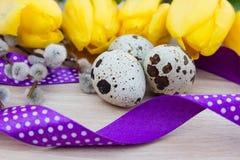 Huevos de codornices en la tabla con las flores y la cinta, cinta Fotos de archivo libres de regalías