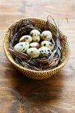 Huevos de codornices en una cesta de mimbre fotos de archivo