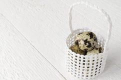 Huevos de codornices en una cesta de mimbre blanca en una tabla de madera blanca, tex imagen de archivo