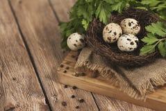 Huevos de codornices en una jerarquía en un fondo de madera Fotos de archivo