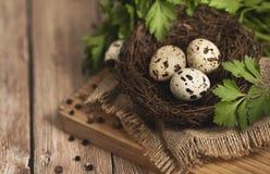 Huevos de codornices en una jerarquía en un fondo de madera Fotografía de archivo