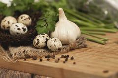 Huevos de codornices en una jerarquía y un ajo en un fondo de madera Imagen de archivo libre de regalías