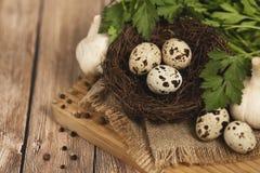 Huevos de codornices en una jerarquía y un ajo en un fondo de madera Imagen de archivo