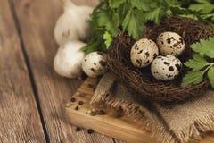 Huevos de codornices en una jerarquía y un ajo en un fondo de madera Fotos de archivo