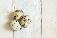 Huevos de codornices en una tabla de madera blanca en una cocina rústica Foto de archivo