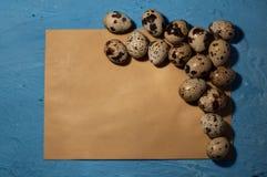 huevos de codornices vacíos del sobre en una textura azul del fondo Imagen de archivo