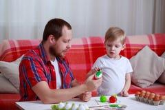 Huevos de la pintura del muchacho y del pap? imagenes de archivo