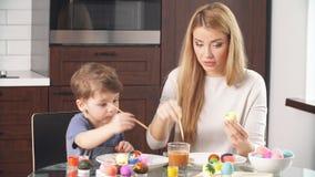 Huevos de la pintura de la madre y del hijo Familia que se sienta en una cocina Preparación para Pascua almacen de metraje de vídeo
