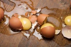 Huevos de la rotura en el piso de madera Fotos de archivo