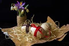 Huevos de madera con una cinta roja en la corteza del abedul Concepto de materiales naturales Los huevos se adornan con las flore Foto de archivo