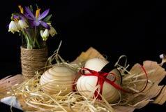 Huevos de madera con una cinta roja en la corteza del abedul Concepto de materiales naturales Los huevos se adornan con las flore Fotos de archivo libres de regalías