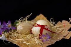 Huevos de madera con una cinta roja en la corteza del abedul Concepto de materiales naturales Los huevos se adornan con las flore Imagenes de archivo