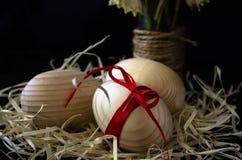 Huevos de madera con una cinta roja en la corteza del abedul Concepto de materiales naturales Los huevos se adornan con las flore Fotos de archivo
