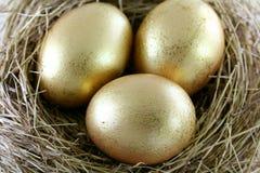 3 huevos de oro con brillos Imágenes de archivo libres de regalías