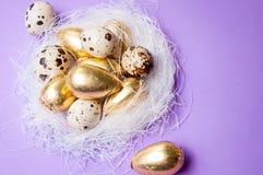 Huevos de oro de Pascua en un fondo azul Fotos de archivo libres de regalías