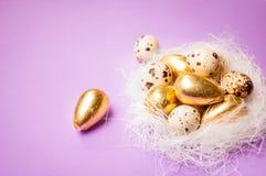 Huevos de oro de Pascua en un fondo azul Foto de archivo