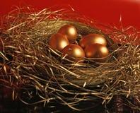 Huevos de oro en fondo rojo Imagenes de archivo