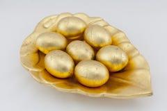 Huevos de oro en una hoja grande Imagenes de archivo