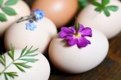 Huevos de Pascua adornados con las hojas y las flores Imagenes de archivo