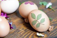 Huevos de Pascua adornados con las hojas y las flores Foto de archivo