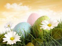 Huevos de Pascua adornados en la hierba con las flores fotos de archivo
