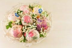 Huevos de Pascua adornados en una cesta Imagen de archivo libre de regalías