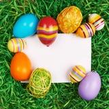 Huevos de Pascua alrededor de la tarjeta blanca Fotos de archivo
