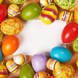 Huevos de Pascua alrededor de la tarjeta blanca Imagenes de archivo