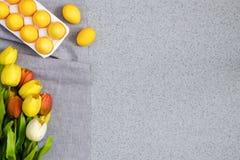 Huevos de Pascua amarillos con un ramo de tulipanes en la sobremesa hecha de piedra de acrílico artificial El concepto creativo d Fotos de archivo