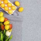 Huevos de Pascua amarillos con un ramo de tulipanes en la sobremesa hecha de piedra de acrílico artificial El concepto creativo d Fotografía de archivo