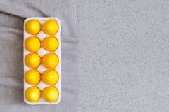 Huevos de Pascua amarillos en la encimera hecha de piedra de acrílico artificial minimalism El concepto creativo de la celebració Imagen de archivo libre de regalías