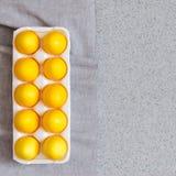 Huevos de Pascua amarillos en la encimera hecha de piedra de acrílico artificial minimalism El concepto creativo de la celebració Imagenes de archivo