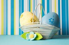 Huevos de Pascua amarillos y azules en una cesta con la flor azul Fotos de archivo libres de regalías