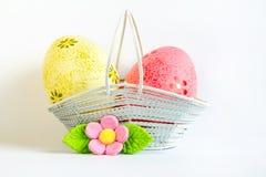 Huevos de Pascua amarillos y rosados en una cesta con la flor rosada Fotos de archivo