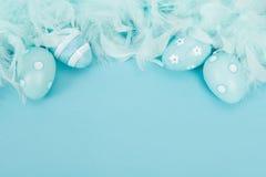 Huevos de Pascua azules de la decoración y plumas azules Imagenes de archivo