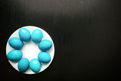 Huevos de Pascua azules en una placa blanca, en un fondo de madera negro Imágenes de archivo libres de regalías