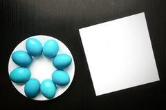 Huevos de Pascua azules en una placa blanca, en un fondo de madera negro Fotos de archivo libres de regalías