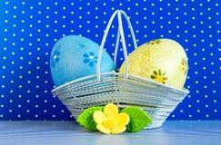 Huevos de Pascua azules y amarillos en una cesta con la flor amarilla Fotos de archivo libres de regalías
