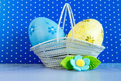 Huevos de Pascua azules y amarillos en una cesta con la flor azul Fotos de archivo libres de regalías