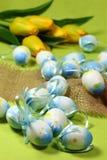 Huevos de Pascua azules y tulipanes amarillos Imagenes de archivo