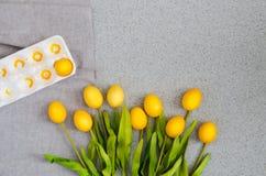 Huevos de Pascua bajo la forma de ramo de tulipanes en la sobremesa hecha de piedra de acrílico artificial El concepto creativo d Foto de archivo libre de regalías