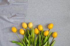 Huevos de Pascua bajo la forma de ramo de tulipanes en la sobremesa hecha de piedra de acrílico artificial El concepto creativo d Fotos de archivo