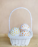Huevos de Pascua blancos con los puntos en pequeña cesta blanca Fotos de archivo libres de regalías