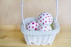Huevos de Pascua blancos con los puntos rojos en pequeña cesta blanca Fotos de archivo