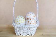 Huevos de Pascua blancos con los puntos rojos en pequeña cesta blanca Imagenes de archivo