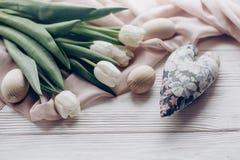 Huevos de Pascua blancos elegantes de los tulipanes y corazón floral en la madera rústica Imágenes de archivo libres de regalías