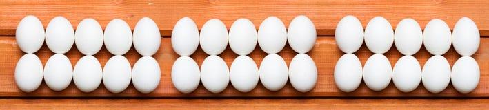Huevos de Pascua blancos en fila en el fondo de madera Fotografía de archivo libre de regalías