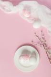 Huevos de Pascua blancos en la placa blanca en un fondo rosa claro Foto de archivo