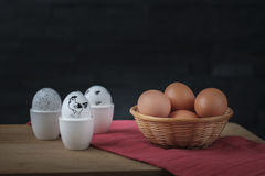 Huevos de Pascua blancos en una huevera y huevos marrones en una cesta Foto de archivo libre de regalías